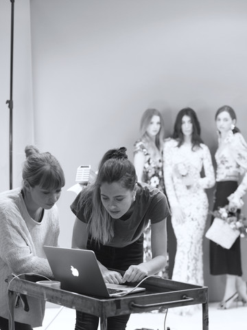 Dos alumnas en un ordenador mientras se realiza un shooting en el fondo desenfocado