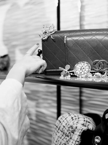 Una vitrina con bolsos y joyería y una mano señalando uno de ellos