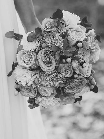 Ramo de flores en primer plano, sostenido por una novia