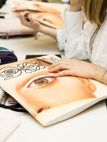 Una carpeta de la marca Loewe sobre un pupitre y una mano sobre ella