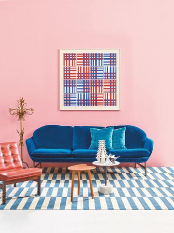 Estilismo de interiores con un sofá azul, un sillón, una mesa y elementos decorativos de distintos colores