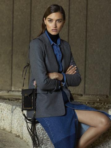 Modelo vestida de ejecutiva, sentada sobre un bordillo de piedra